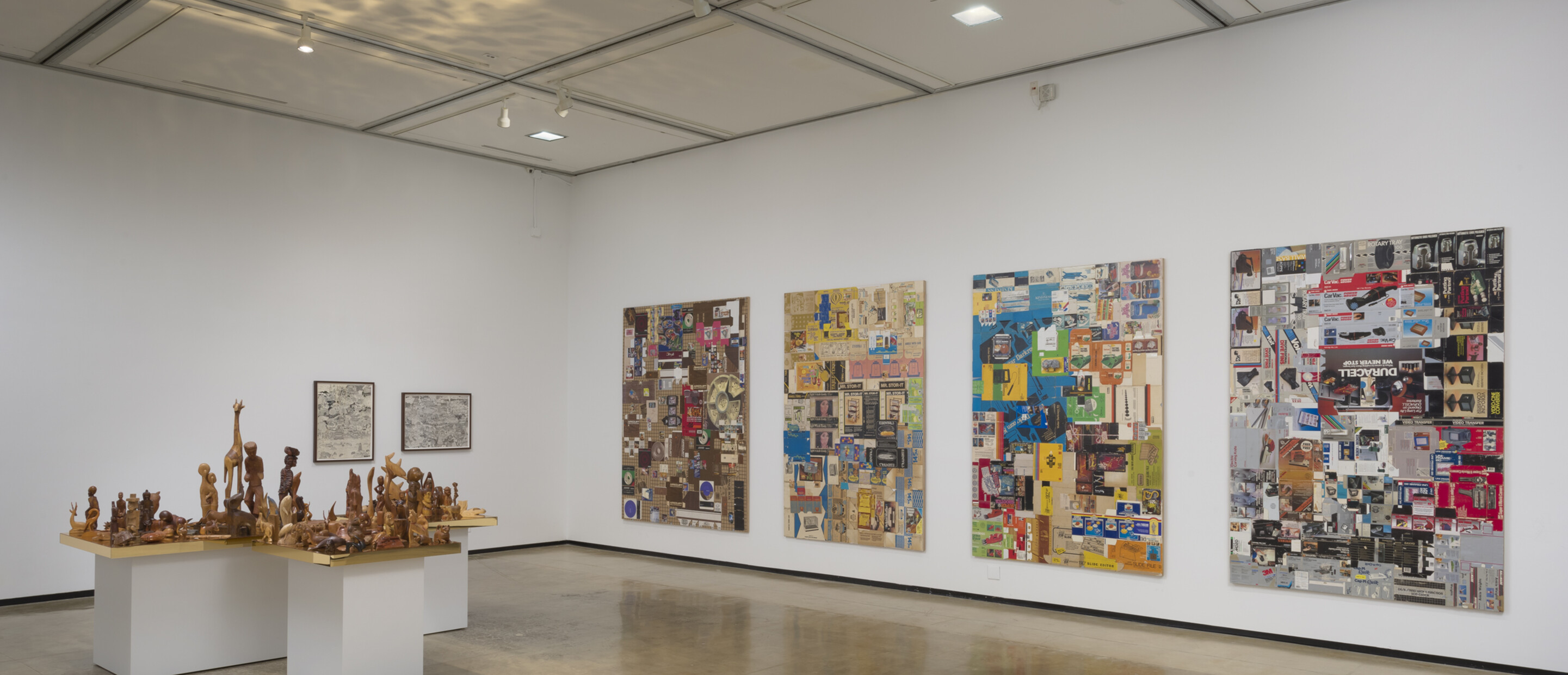 Installation view of R.S.V.P. Los Angeles with 4 multi-media works on the wall and table with multiple wooden sculptures