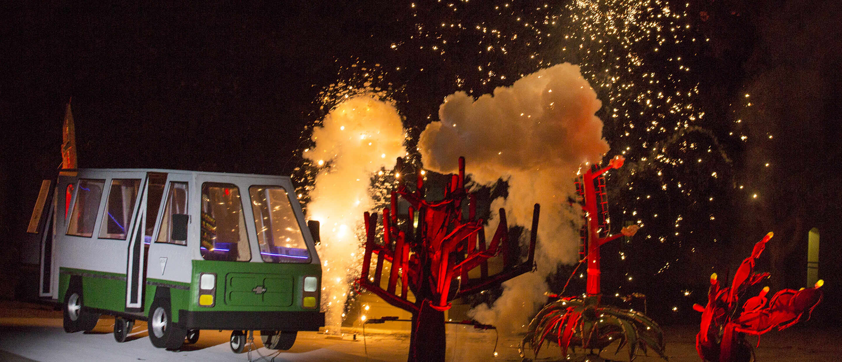 Papermaché microbus and cacti being blown up using pyrotechnics