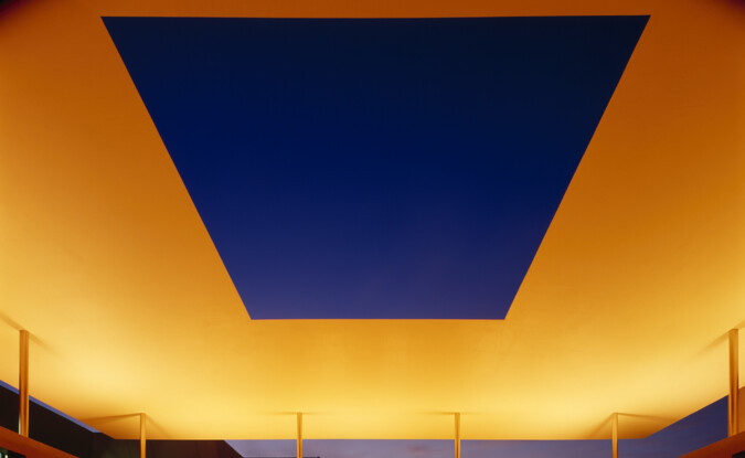 yellow-orange lighting on roof structure with square opening over a pool