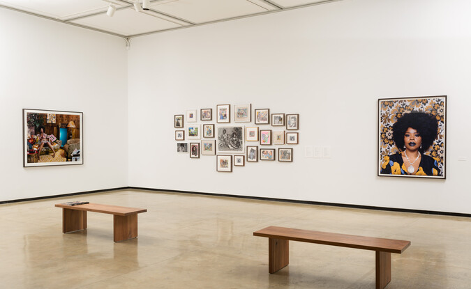 Installation view of a gallery with photographs and montage of 2-dimensional works with 2 wooden benches on the floor