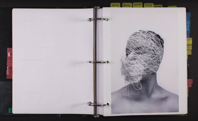 3-ring binder open to a blank page and another with photograph of figure wrapped in string