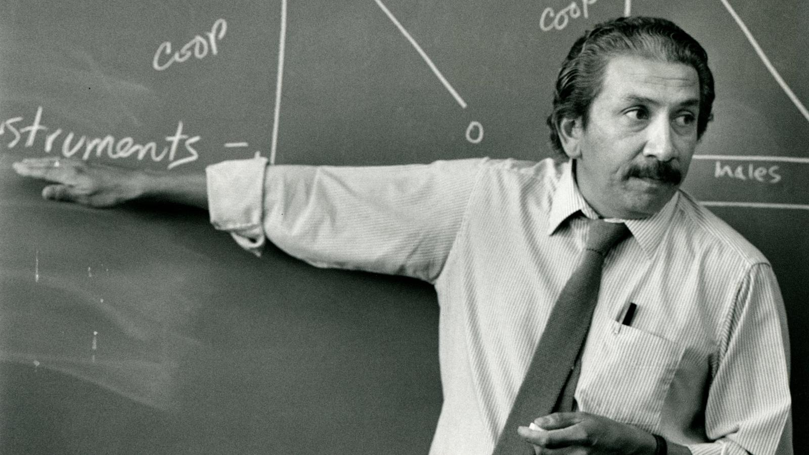 Ray Buriel teaching in front of a chalkboard.