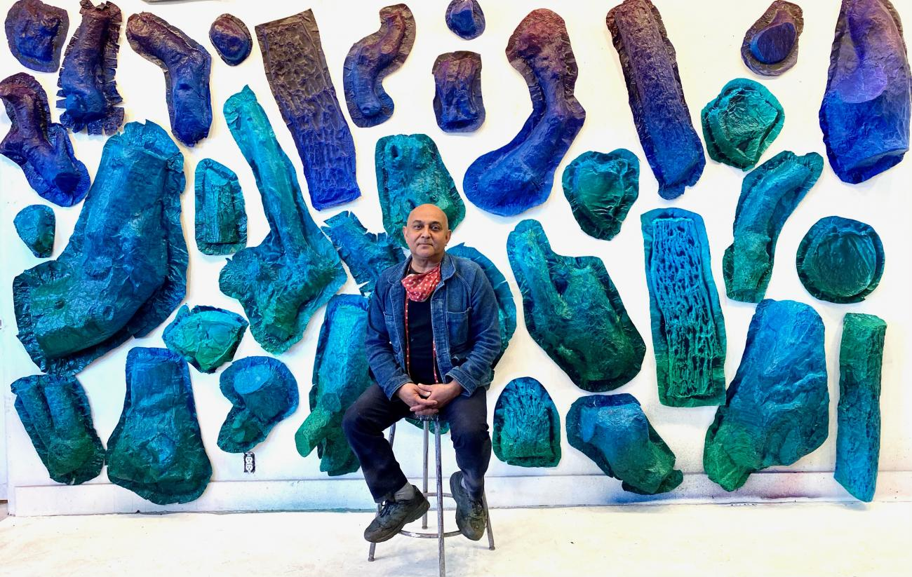 Artist Sandeep Mukherjee seated in front of blue-hued components of his YouTube Theater installation.