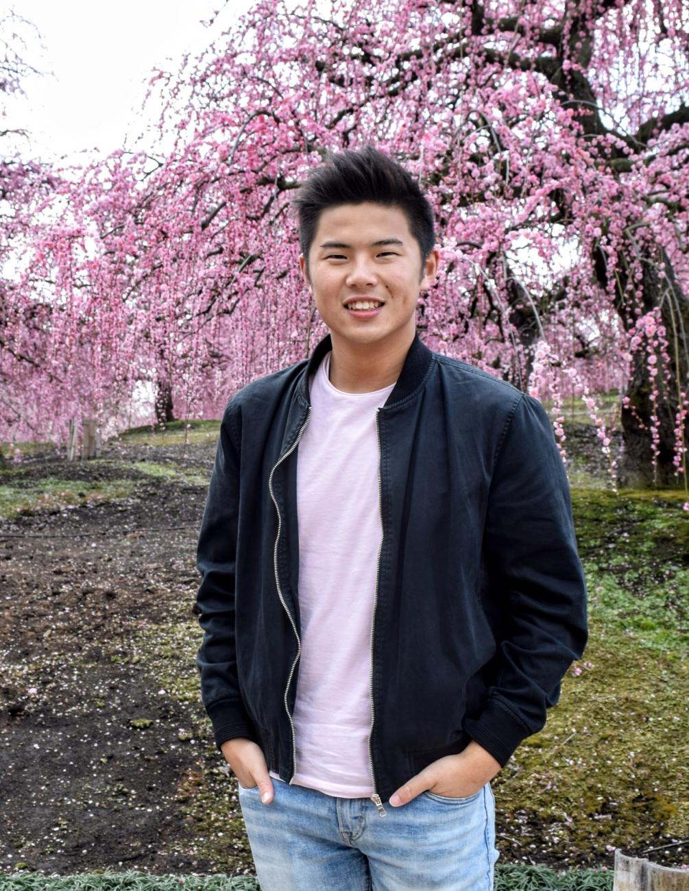 Brandon Tran in front of blossoming cherry trees