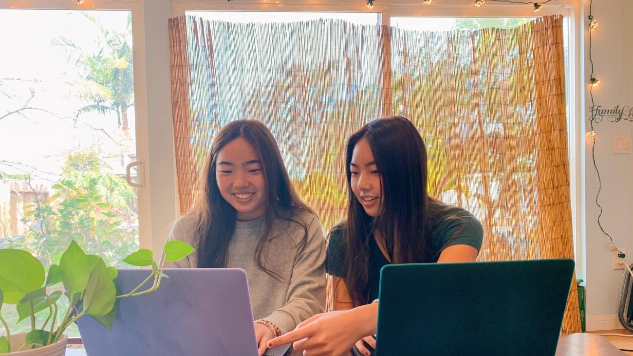 Summer and Evelyn Hasama working on their laptops.