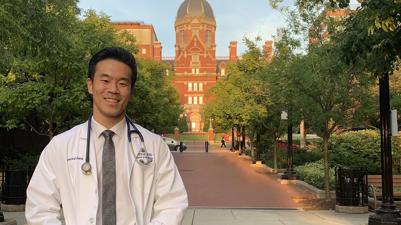 Howard Chang '14 in medical white coat at Johns Hopkins University