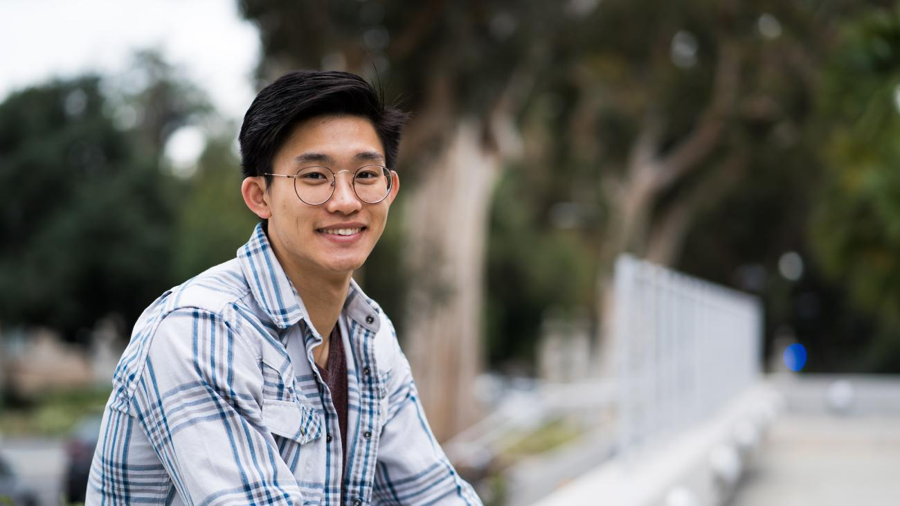 Lawrence Chen sits on a bench.