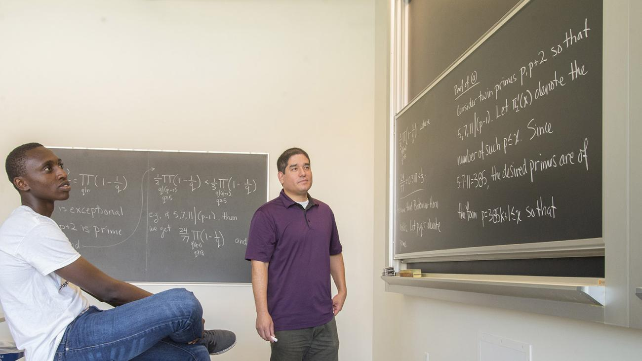 A student is sitting on a table looking at a chalkboard while a professor stands in the middle.