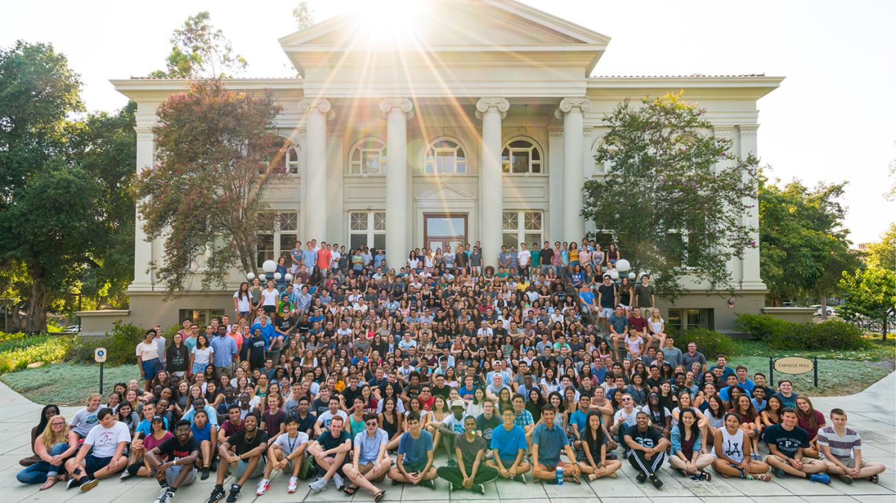 The student class of 2020 sitting in front of the Carnegie building.