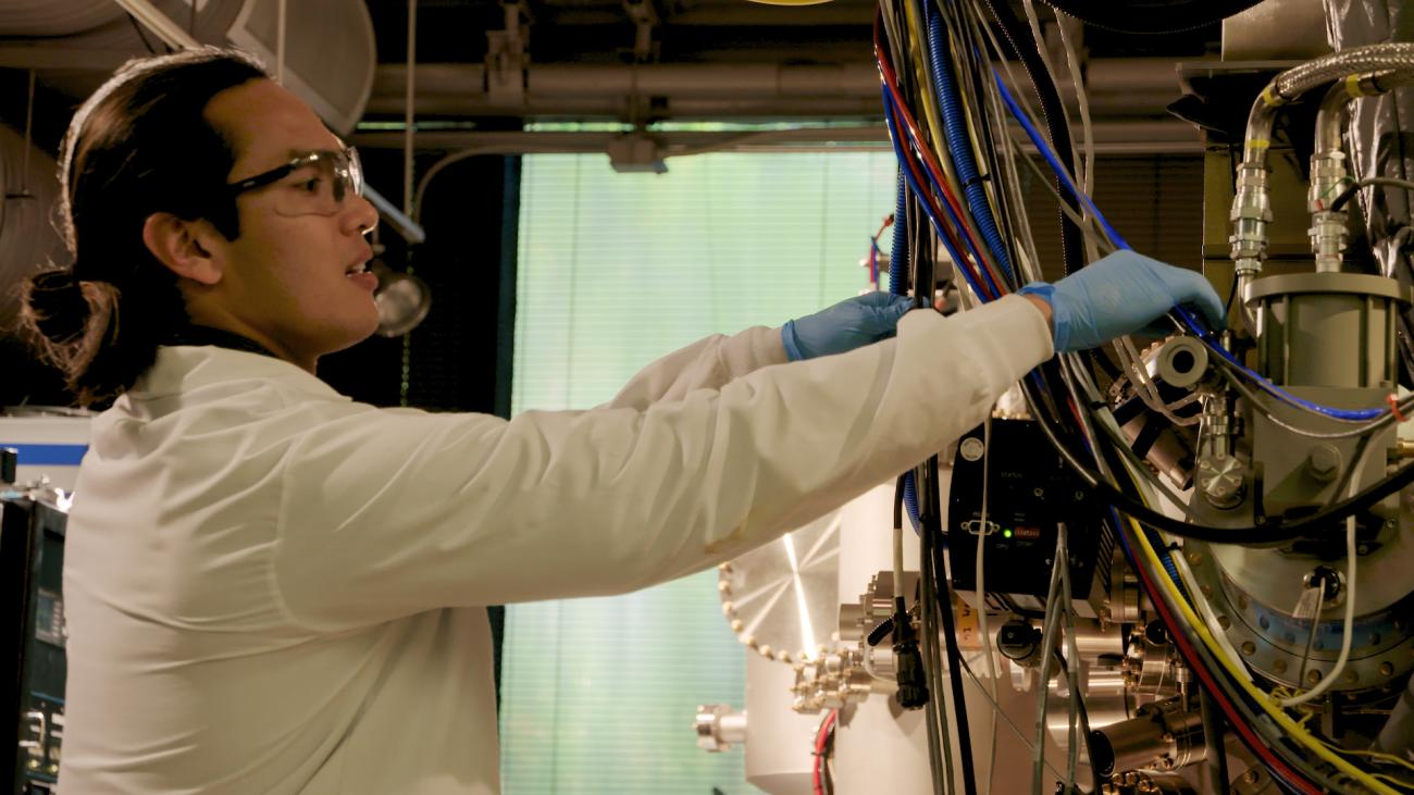 Scott Tan in profile in lab gear is working with computer wires.